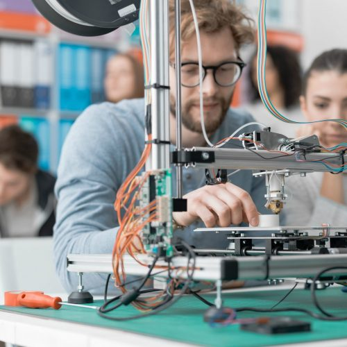 Engineering students using a 3D printer in the lab, learning and technology concept